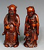 A pair of Chinese bamboo carvings of elderly sages, one holding a fan, the