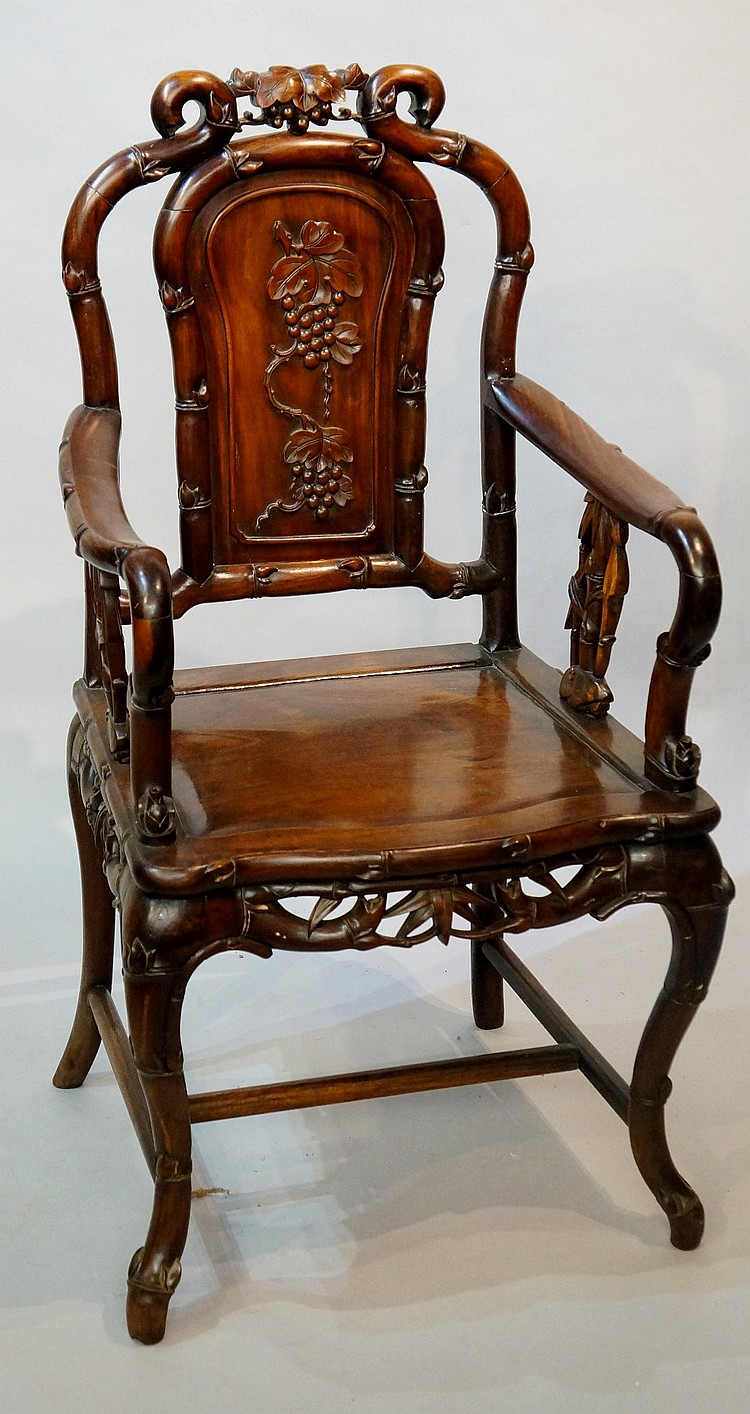 A Chinese hardwood armchair, the shaped waisted back carved with vine leave