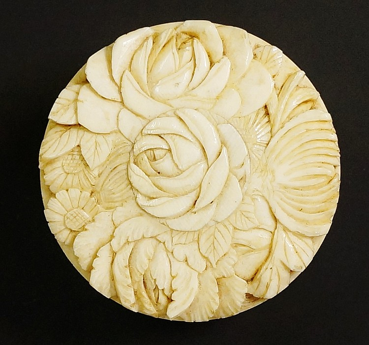 A late 19th Century Japanese circular carved ivory box, the pull-off lid fi