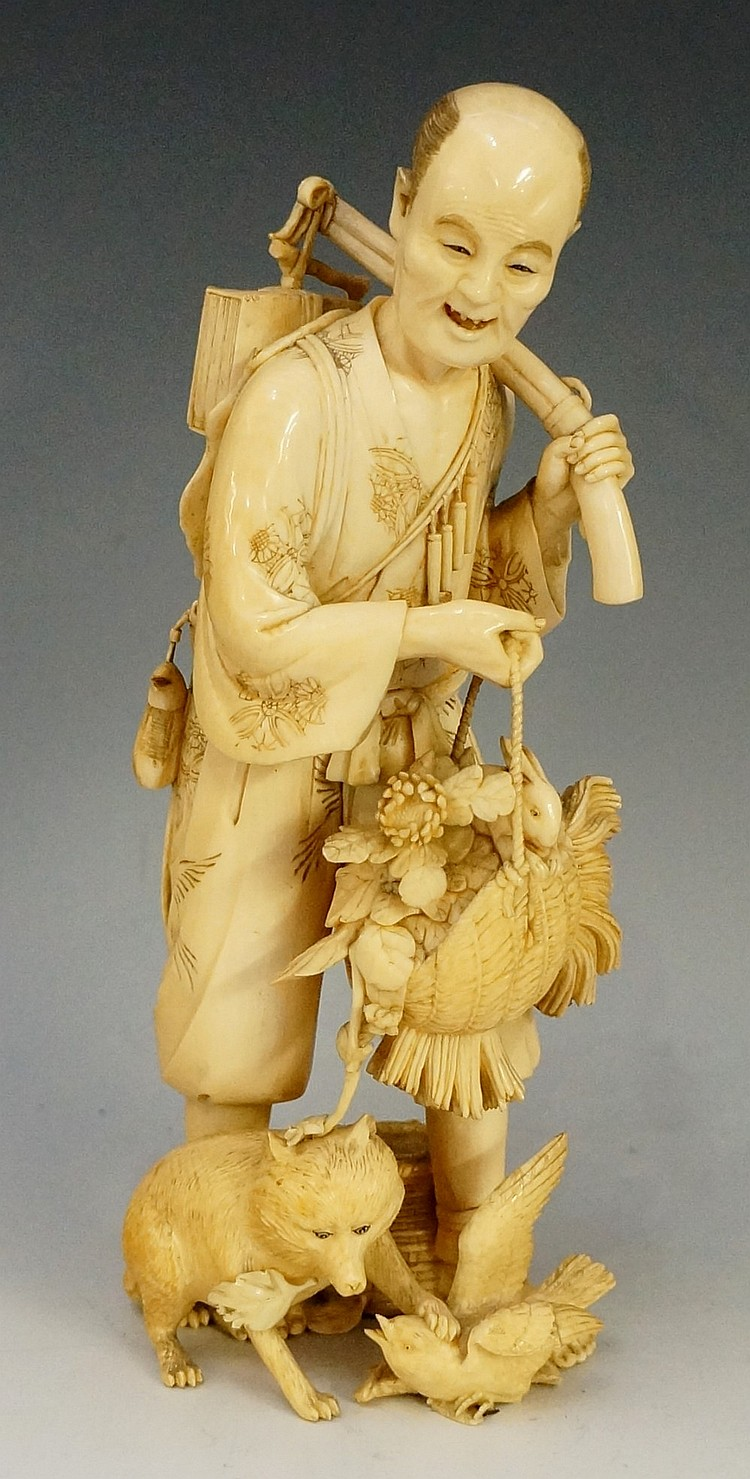 A Japanese single piece ivory carved figure of a traveller with basket of c