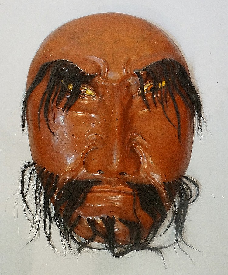 An unusually large Japanese red lacquer mask or wall sculpture finely carve