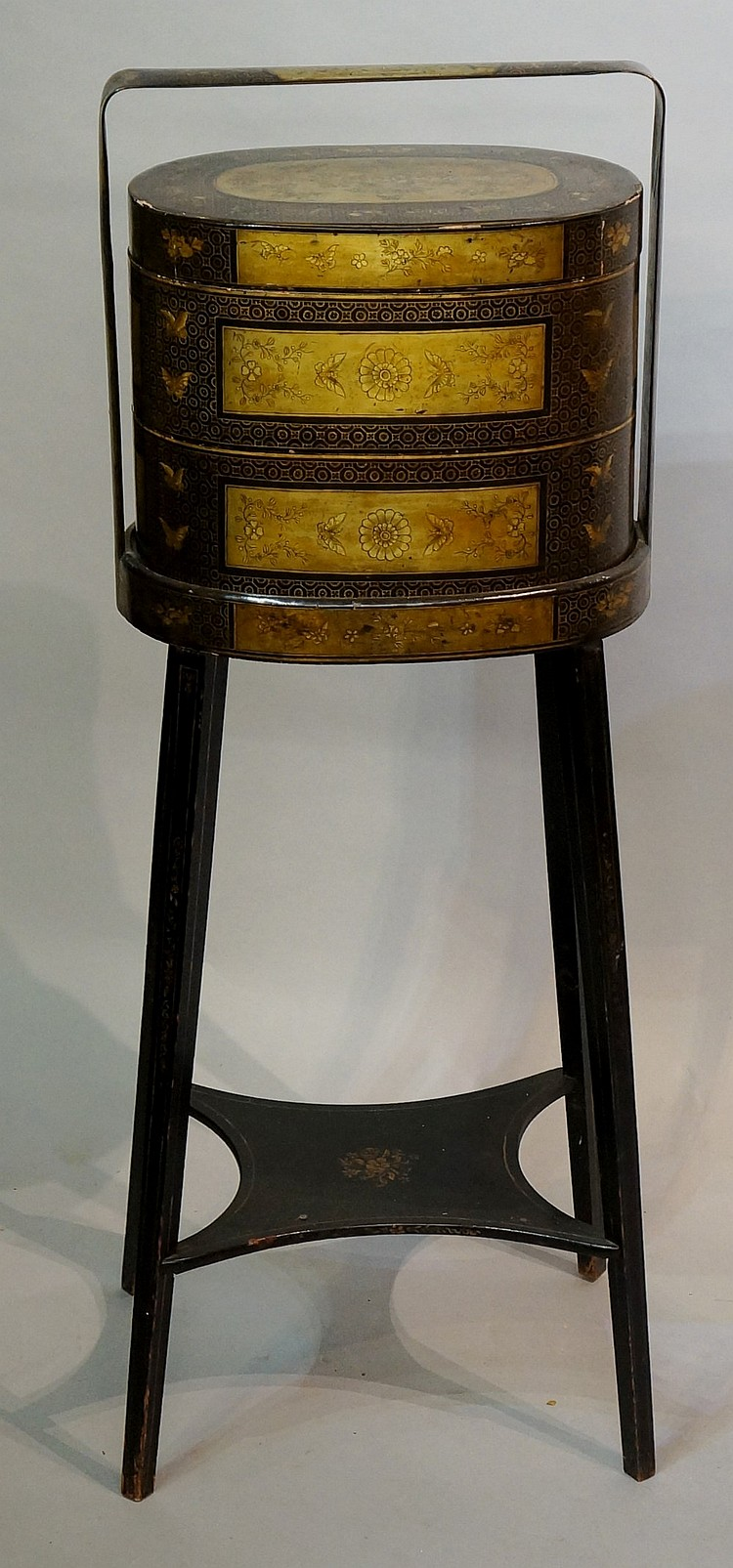 A 19th Century Japanese black lacquer cabinet on stand, the oval three tier