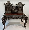 An ornate Japanese stained wooden desk of concave fronted form, the rear su