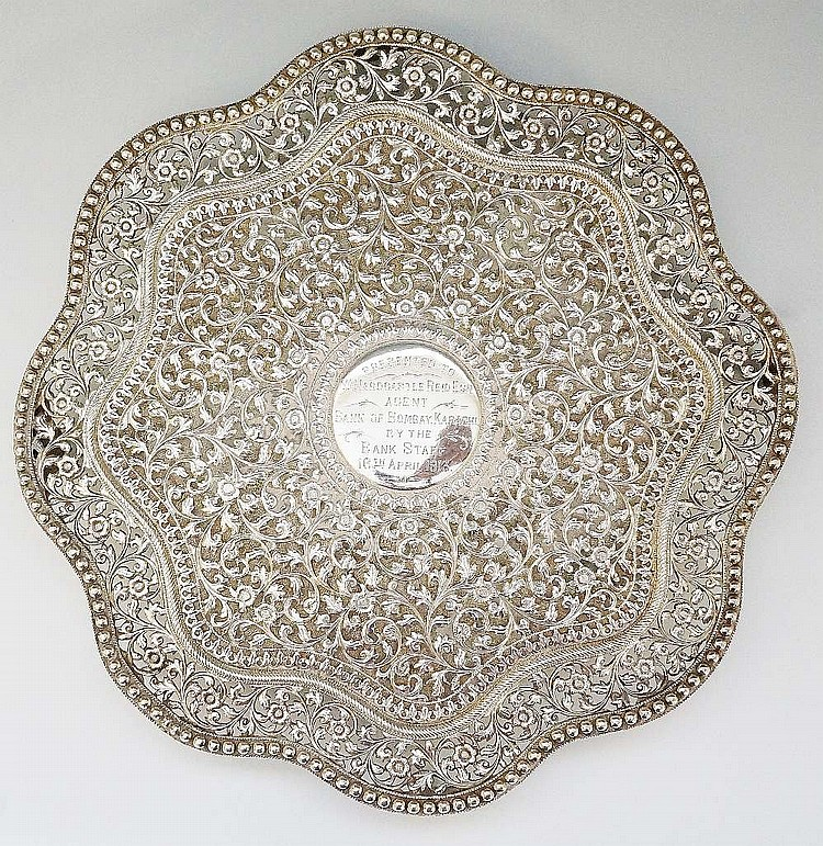 An Indian silver coloured metal salver, elaborately chased and embossed wit