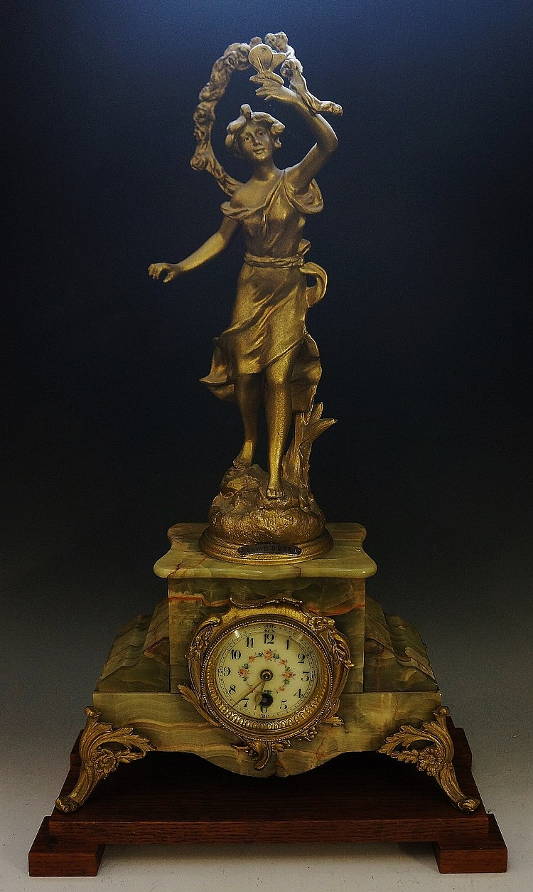 A late 19th Century French gilt metal and onyx mantel clock, the onyx venee