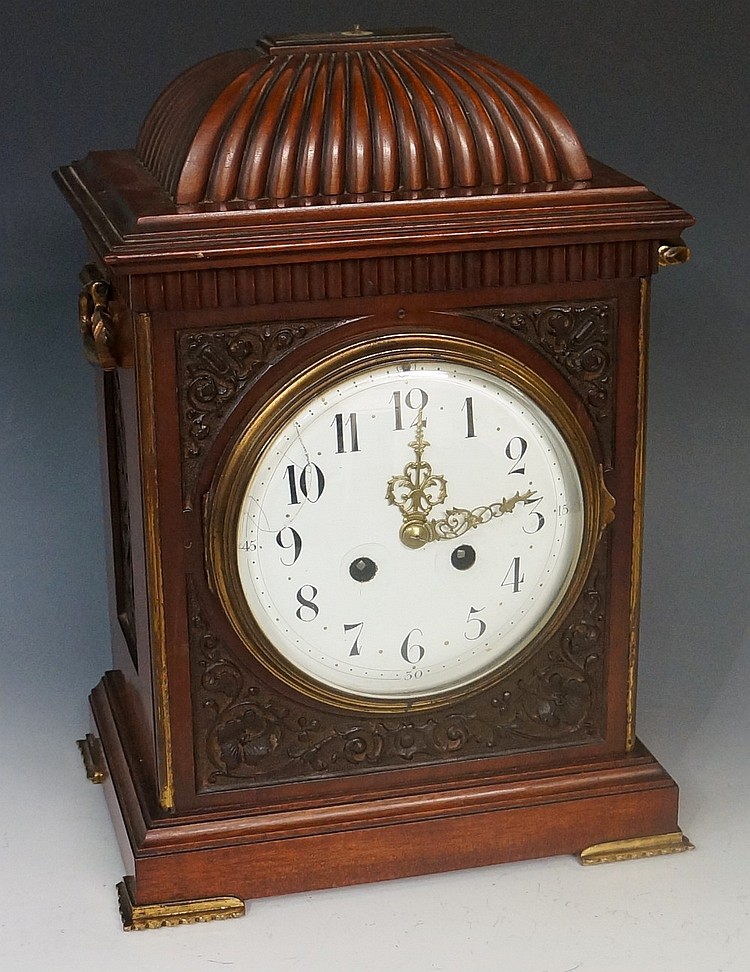 A George II style mahogany bracket clock, the fluted domed top with pineapp