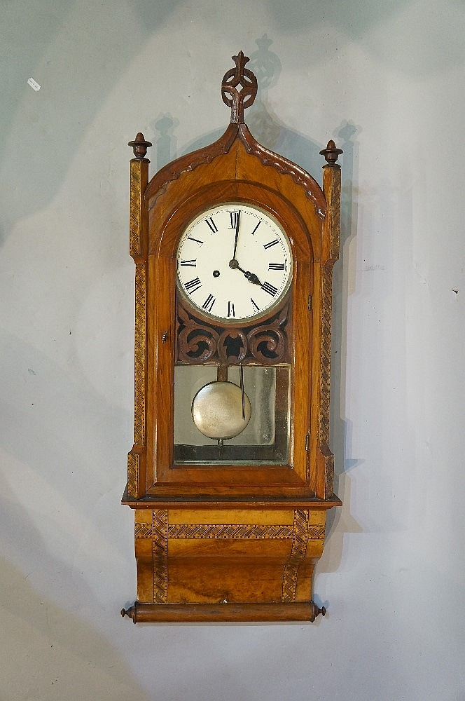 A Victorian walnut veneered drop case wall clock with ''Gothic'' top flanke