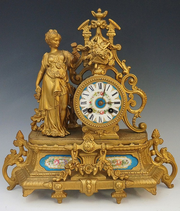 A late Victorian gold painted white metal mantel clock, the cylindrical cas
