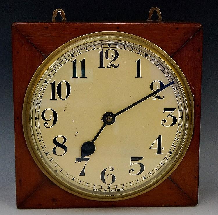 An English electric wall clock, the square mahogany case enclosing a circul