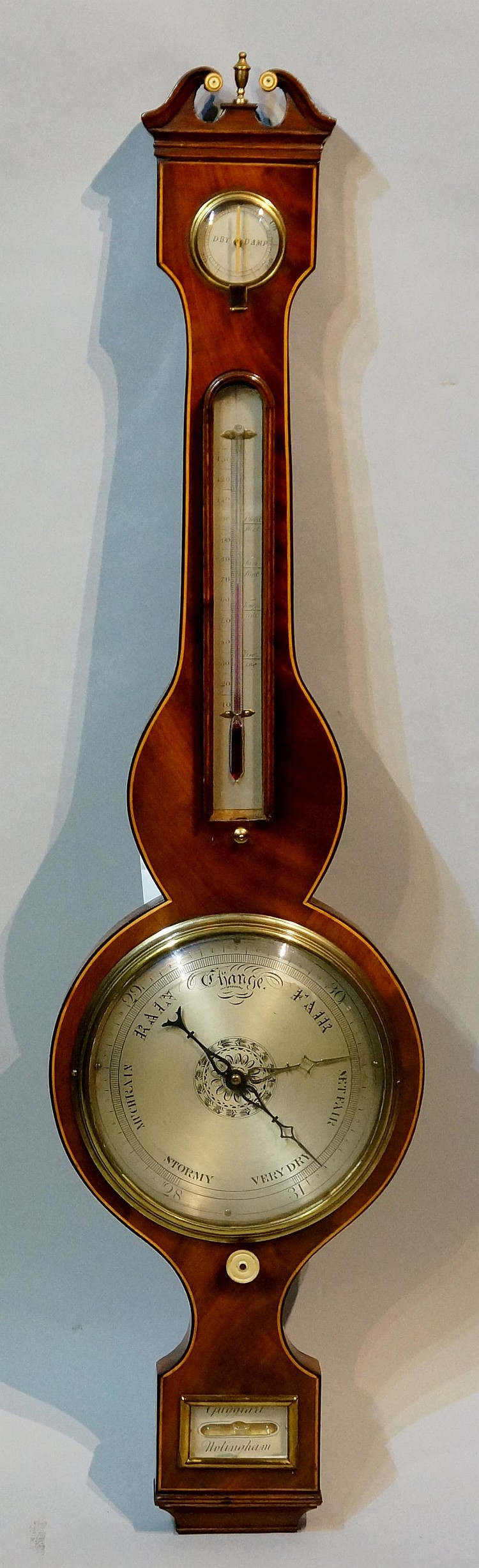 A George III mahogany wheel barometer with thermometer, outlined throughout
