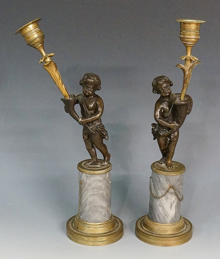 A pair of Regency bronze candlesticks modelled as infants holding cornucopi