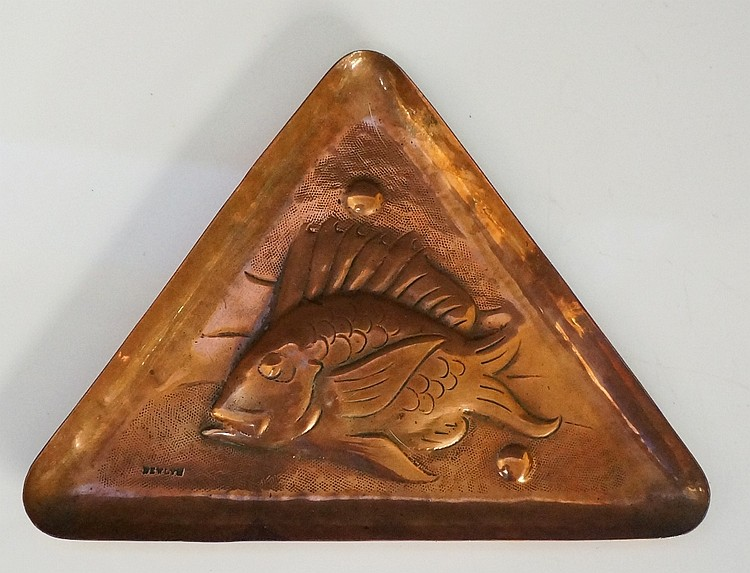 A Newlyn School copper triangular dish, embossed with a stylised fish on a