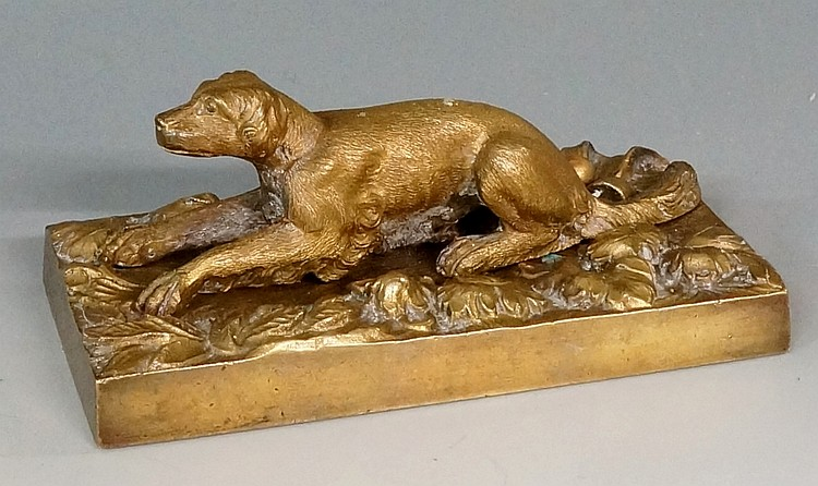 An early 19th Century bronze model of a recumbent dog on a leaf cast base,