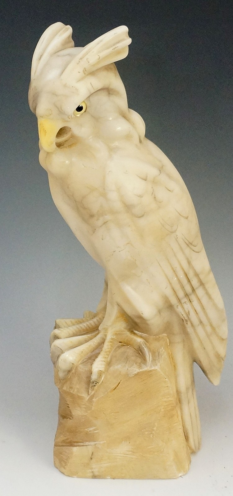 A carved alabaster bird of prey with glass eyes standing on a rocky base, 3