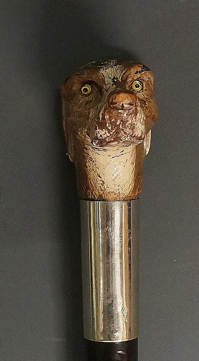 An early 20th Century walking stick, the wooden handle carved and painted a
