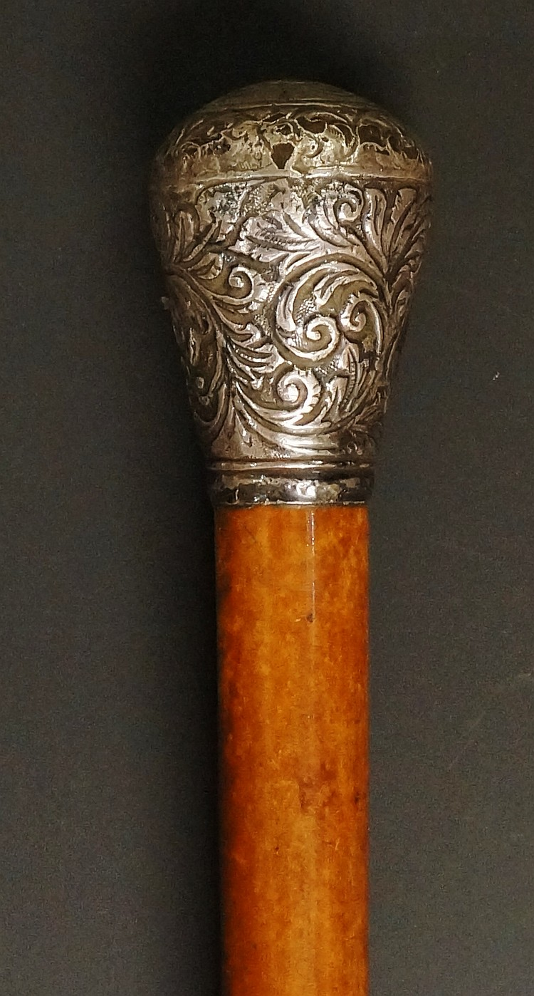 A Victorian walking stick, the silver coloured metal pommel chased and repo