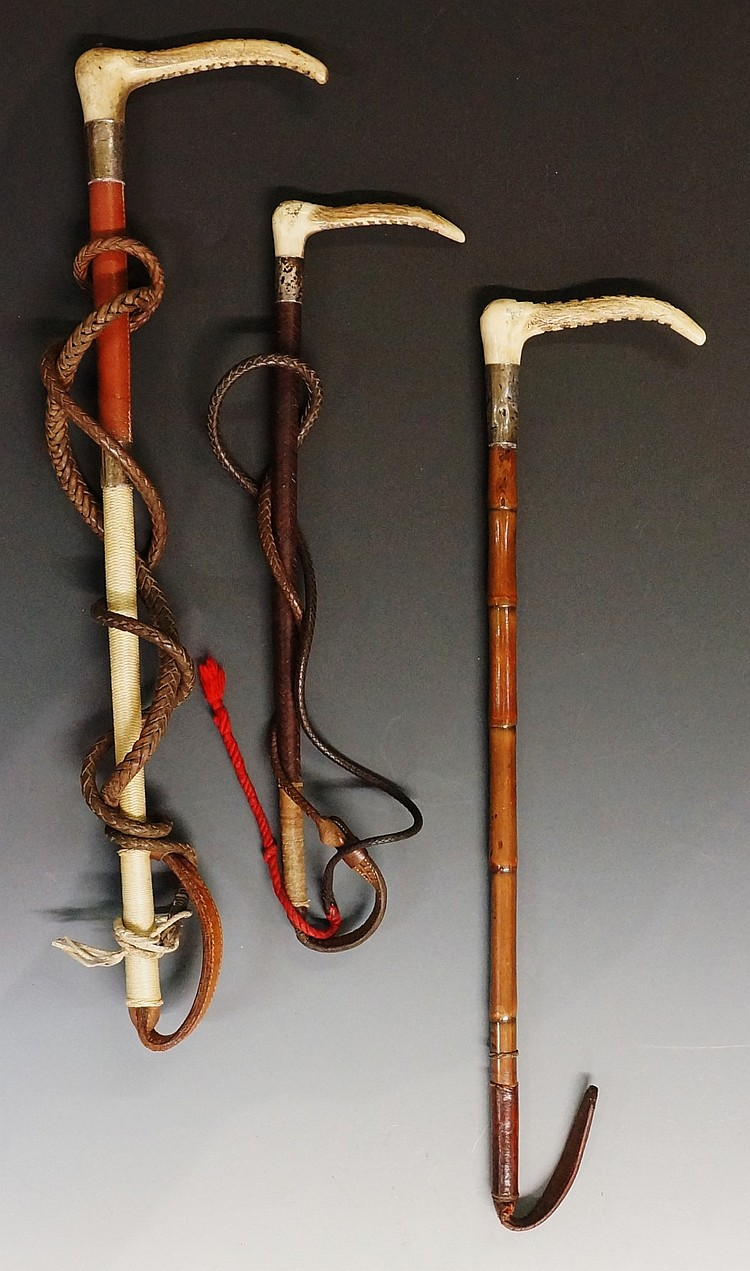 A selection of three hunting whips, all with antler handles and silver coll