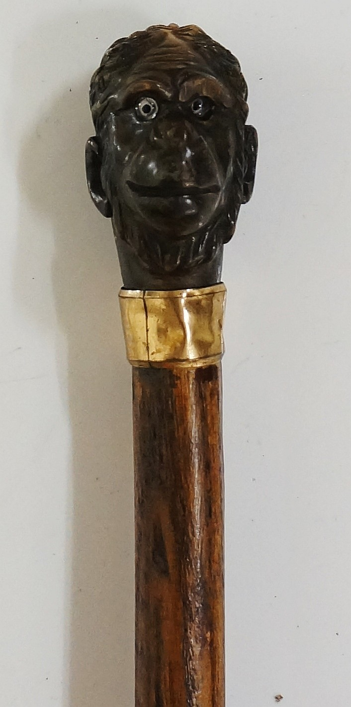 A late 19th / early 20th Century walking stick, the horn handle carved as a