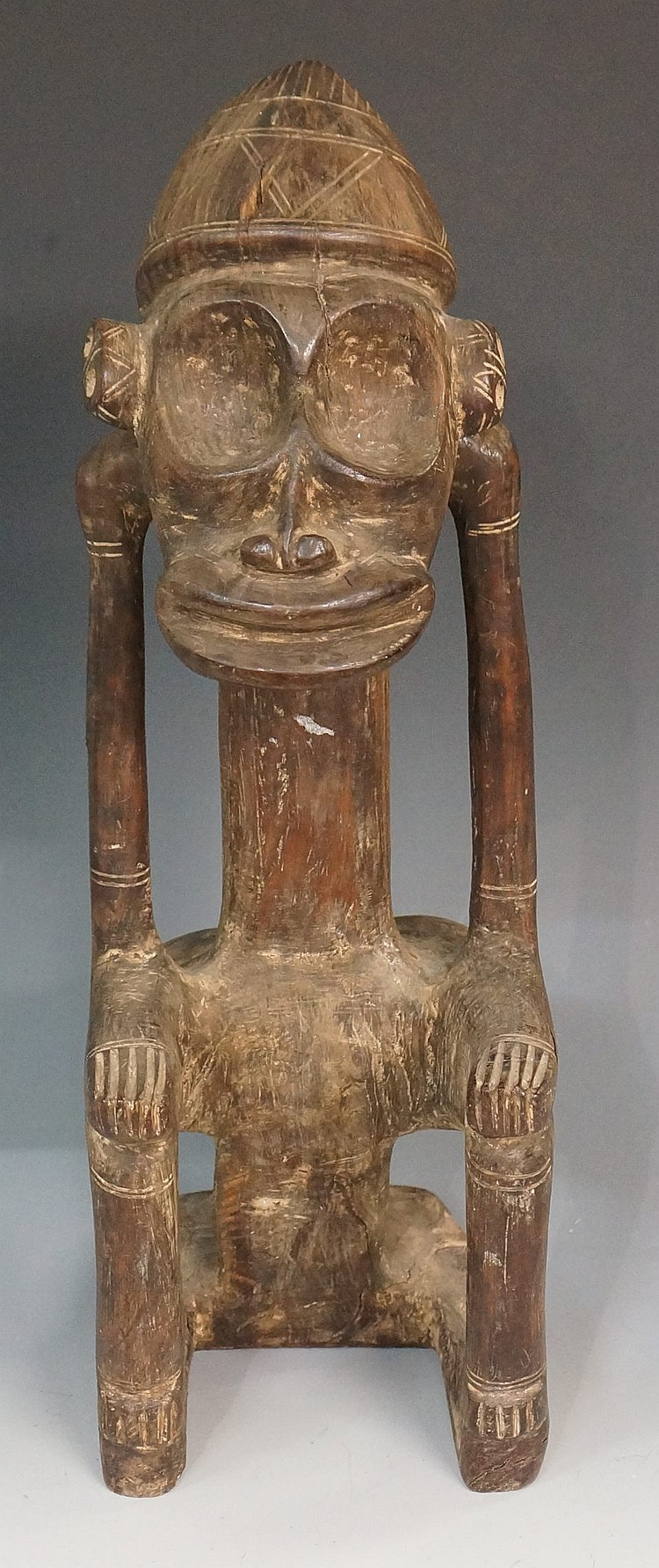 An African tribal seated figure, the face with dished eyes and wide mouth,