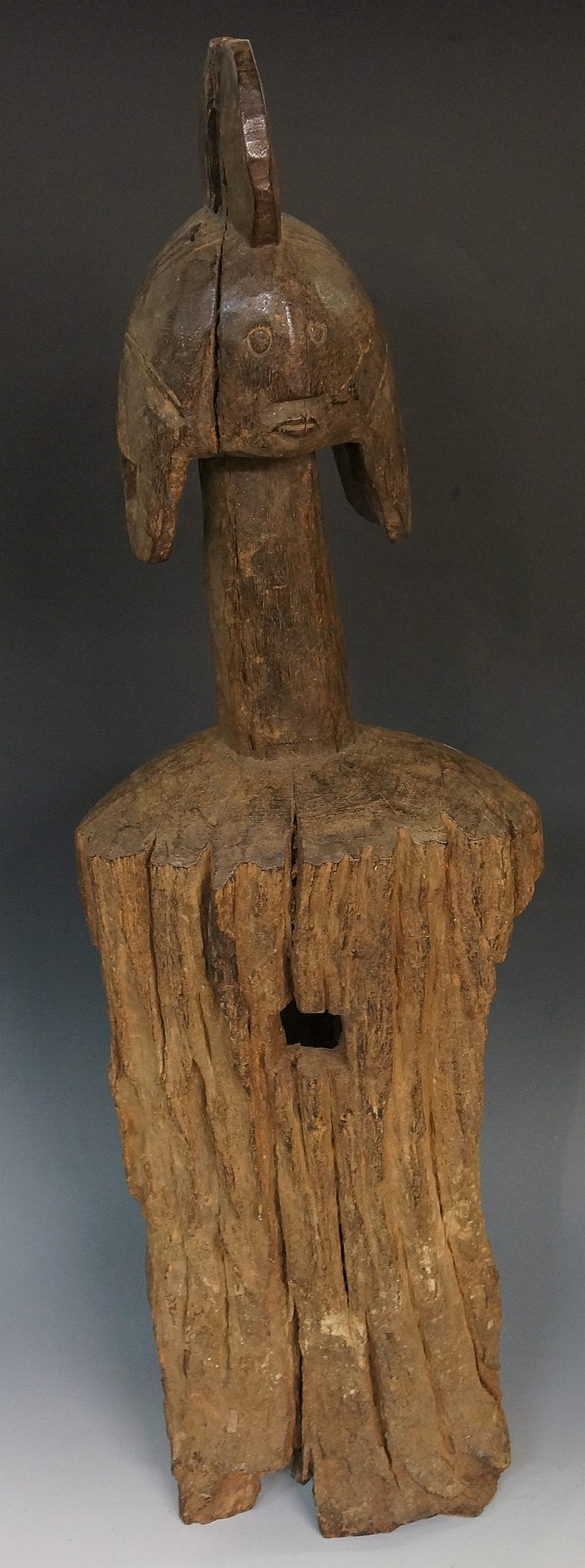 An African trunk carved tribal figure, the head with stylised headdress and