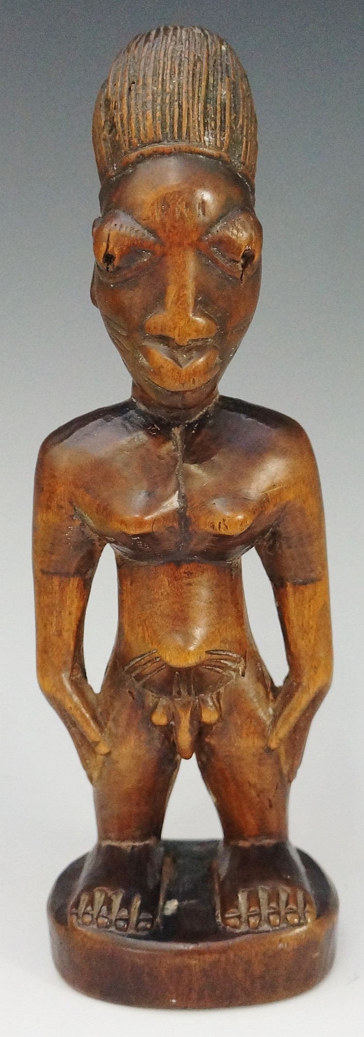An African tribal figure of a man, standing, his hands on his hips, 25cm hi