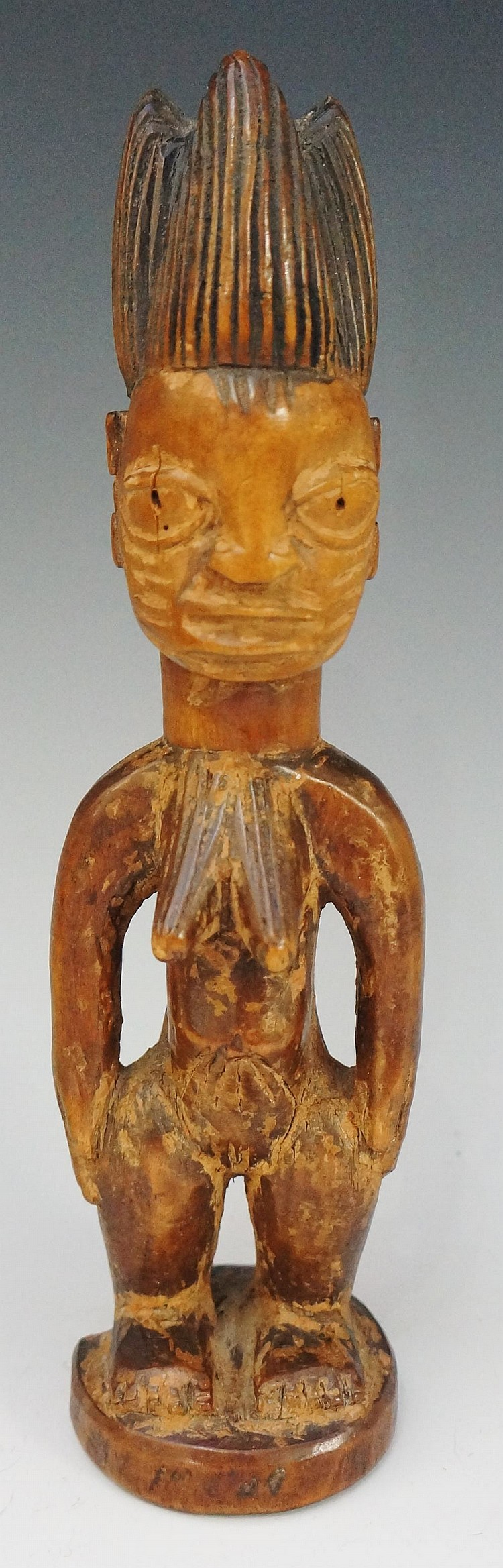 An African tribal figure of a female, with hands on her hips, ornate hair,