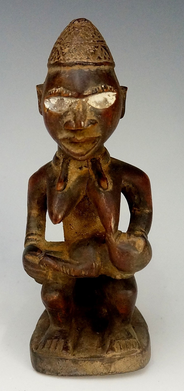An African carved wooden figure of a female seated form with suckling infan