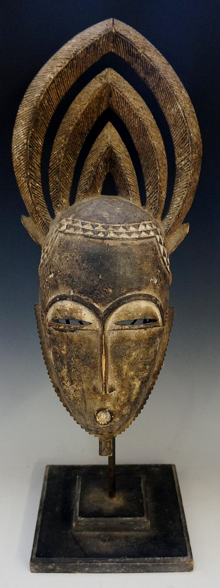An African tribal mask with ornate carved headdress, mounted on a stand, 56