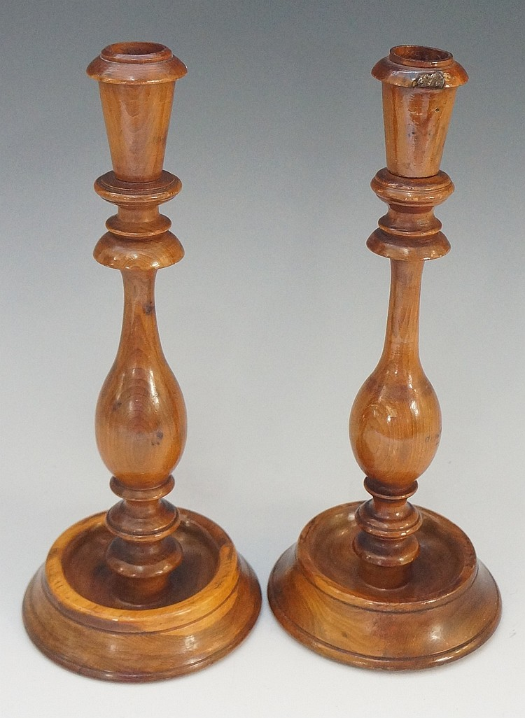Treen - a pair of yew wood candlesticks with tapered cylindrical nozzles an