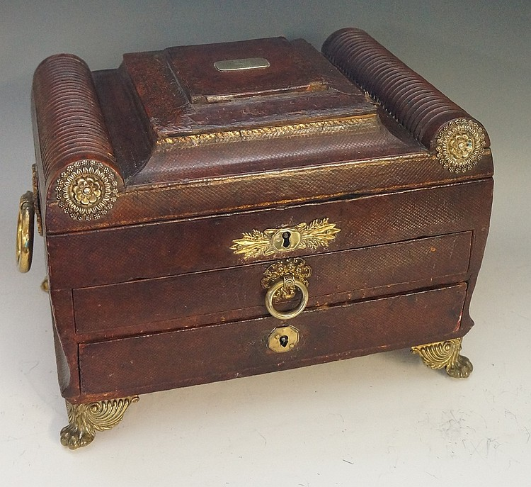 A Regency leather cased workbox of sarcophagus shape the hinged lid with ra