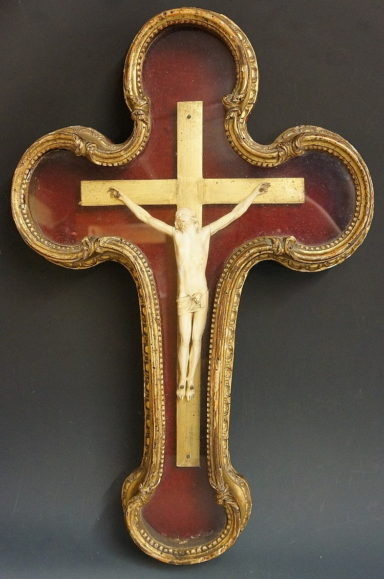 A 17th Century continental carved ivory corpus on a gilt wooden cross conta