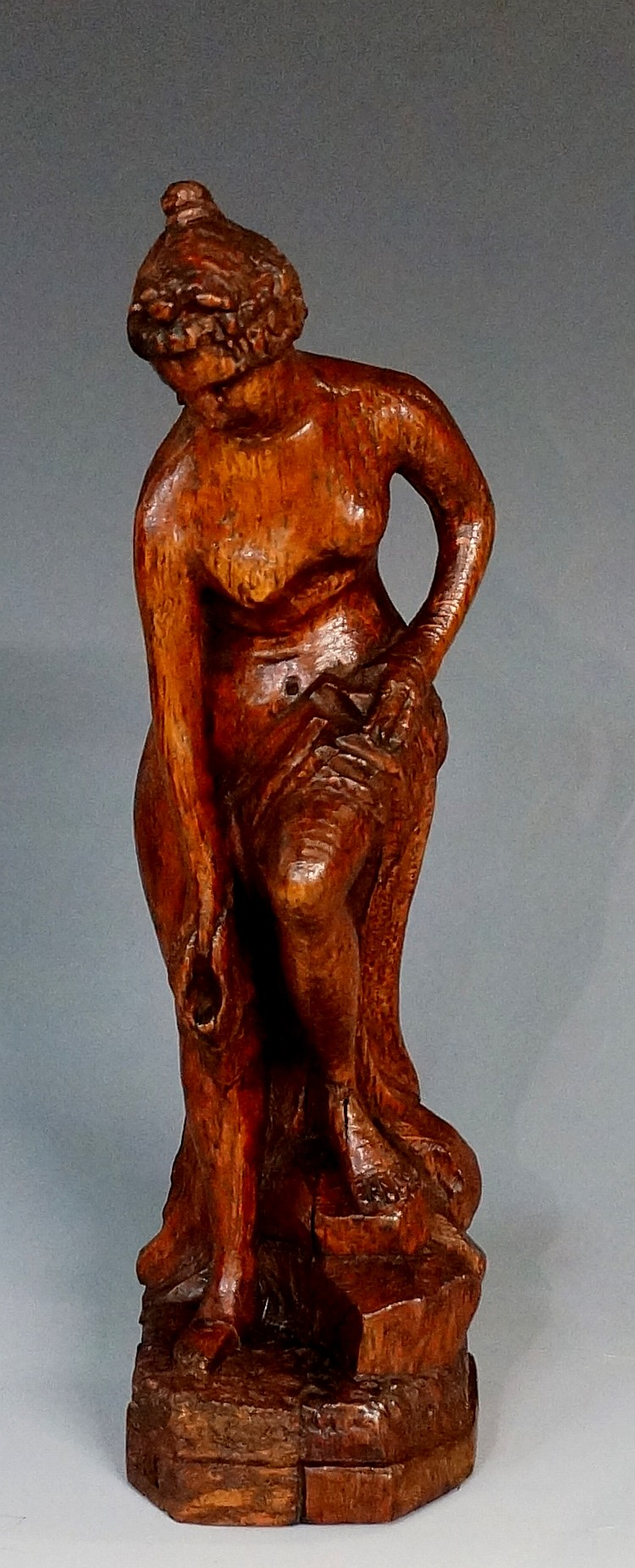 A 19th Century oak carving of a naked female bather with towel across her l