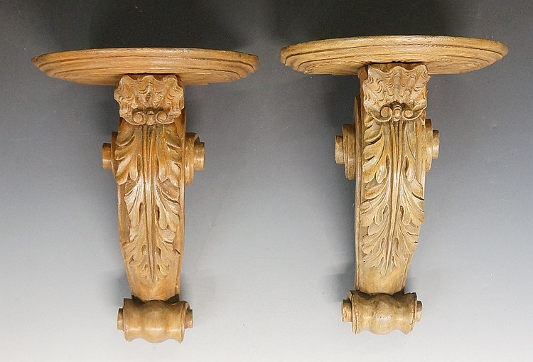 A pair of carved softwood wall brackets, the D-shaped tops above shell and