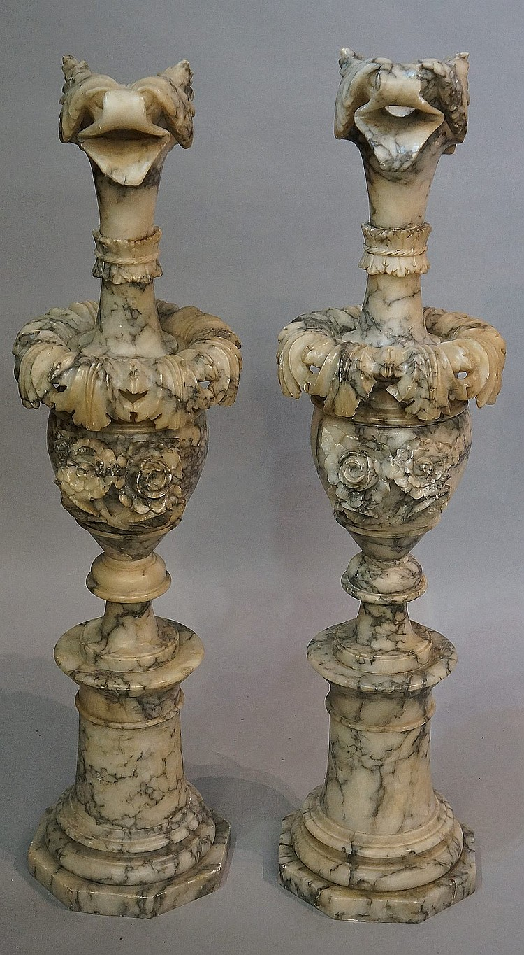A pair of veined alabaster urns with leafy bird spouts, the waisted necks w
