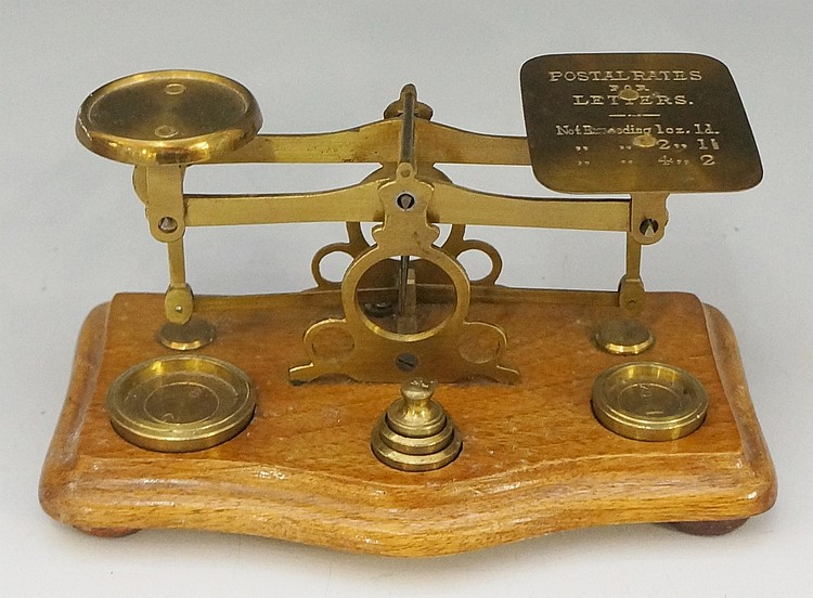 A set of brass postal scales, the shaped rectangular base with serpentine f