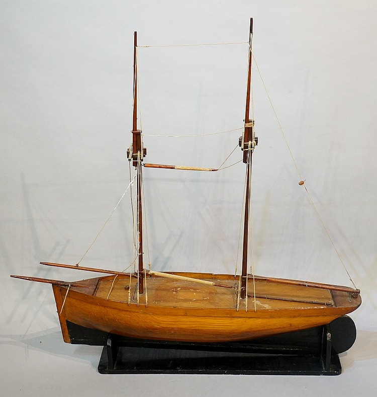A late 19th / early 20th Century two masted wooden hulled model boat on a b