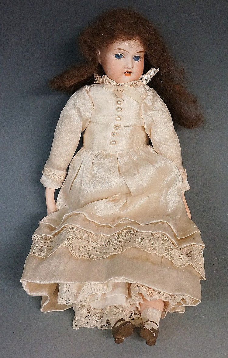 An Armand Marseilles porcelain headed doll with fixed blue eyes, stuffed fa