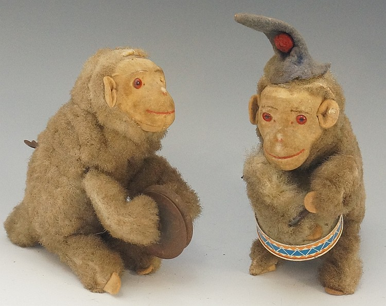 Two German clockwork plush monkey musicians, one playing a drum the other c