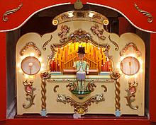 A hand built musical fairground organ, the red painted hut shaped case cont