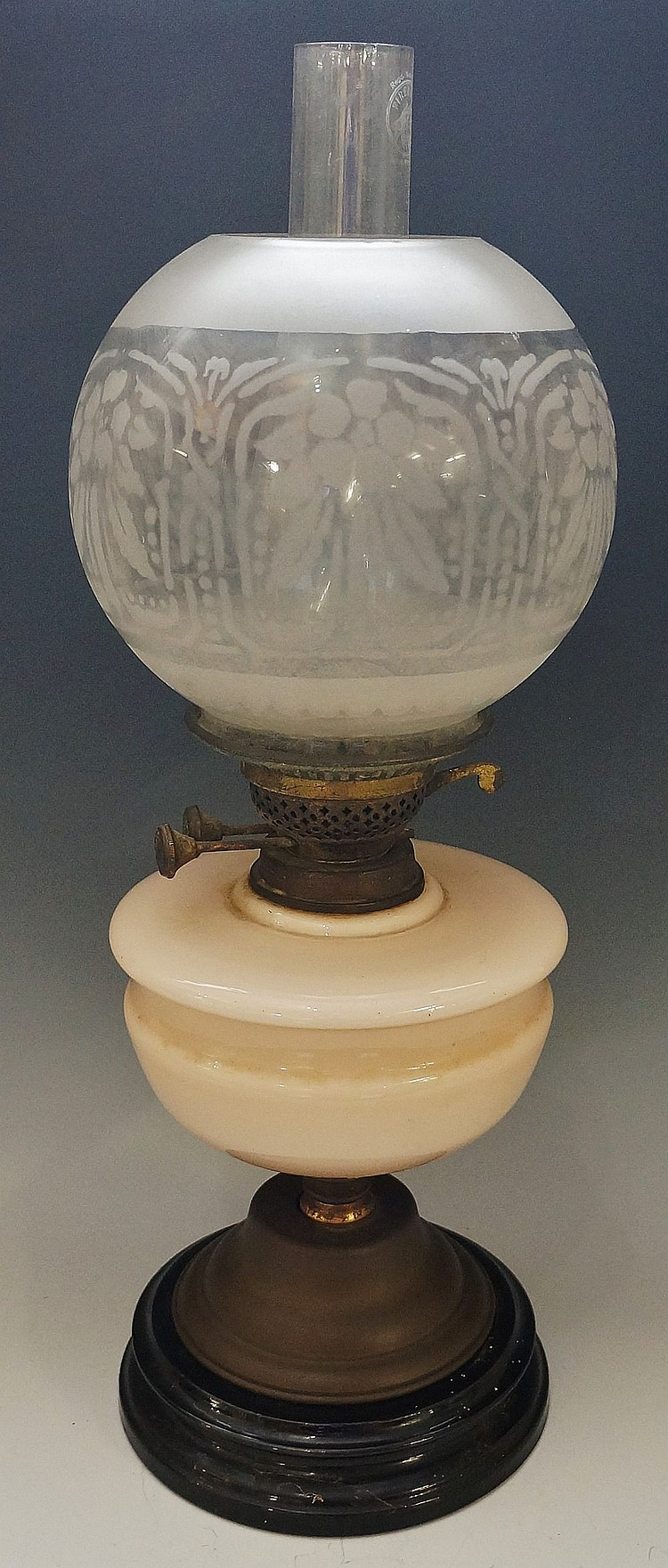 A Victorian oil lamp with pink glass reservoir and acid etched frosted glob