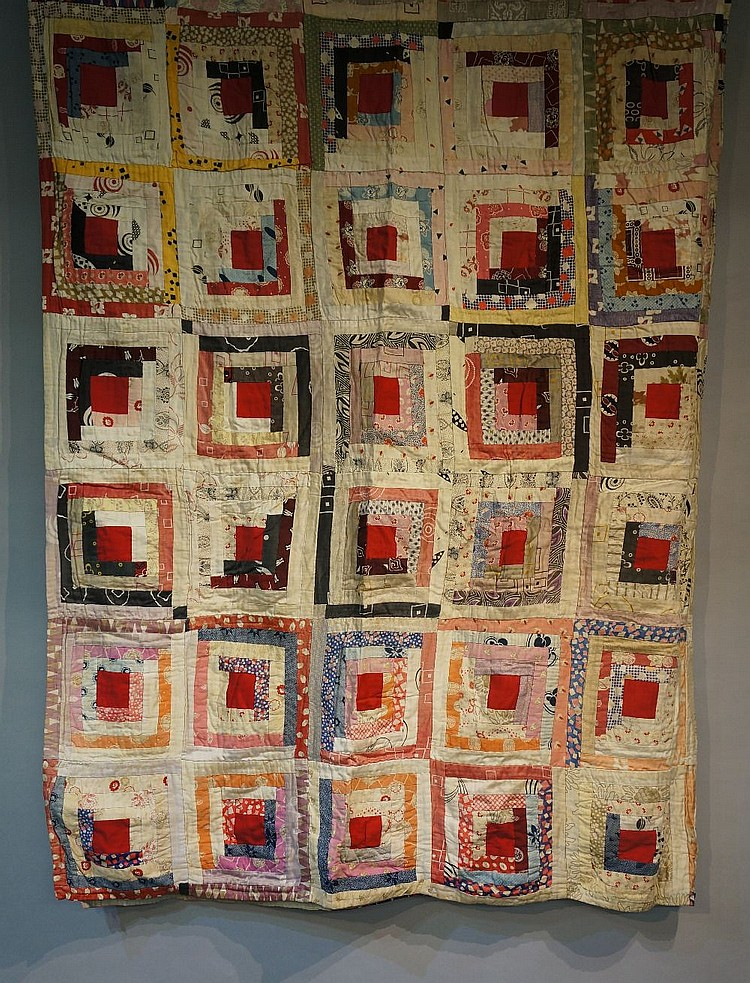 An early to mid 20th Century log cabin patchwork quilt made up of ten by ni