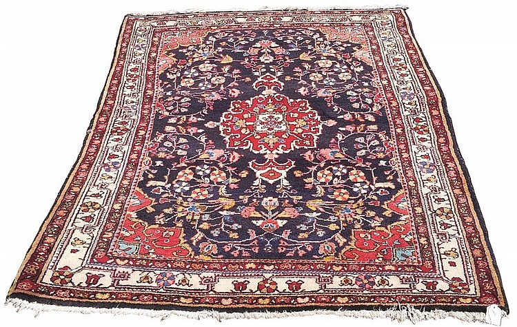 A Persian Bebahan rug, central red floral medallion on dark blue ground wit