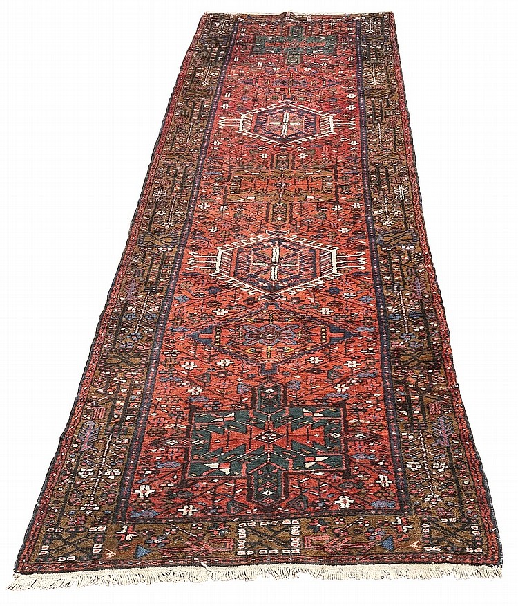 A Persian Heriz runner, seven geometric medallions of various colours on re