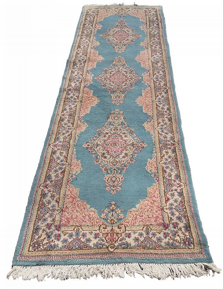 A good Kirman runner, three floral diamond shaped medallions on light blue