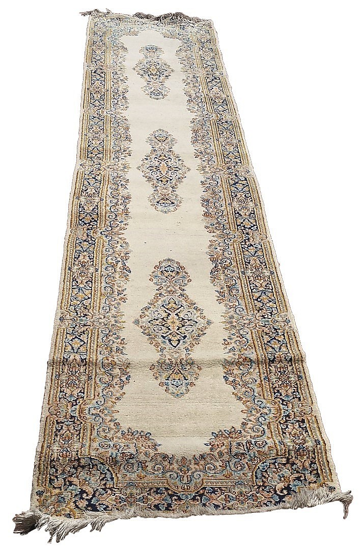 A Persian Kirman runner, three floral yellow and blue medallions on cream g