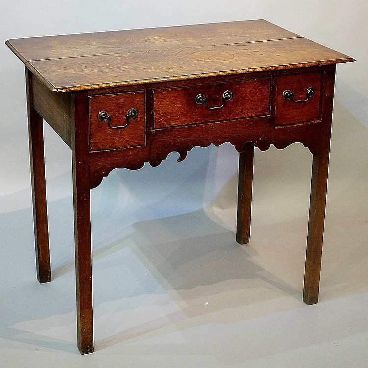 An early George II oak lowboy, the rectangular over sailing top above one l