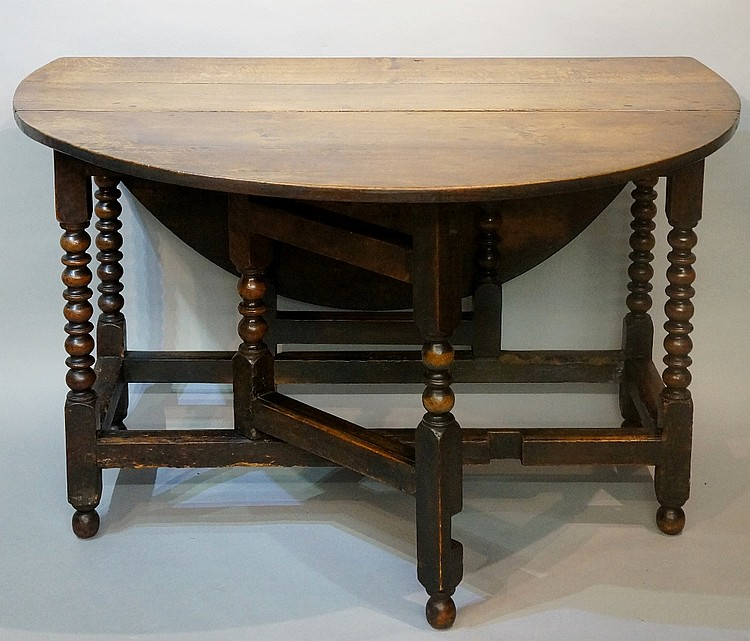 An oak gate leg table, the oval top above single frieze drawer on bobbin tu