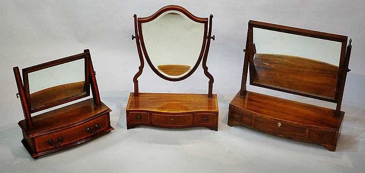 Three dressing table mirrors including: a George III mahogany serpentine sh
