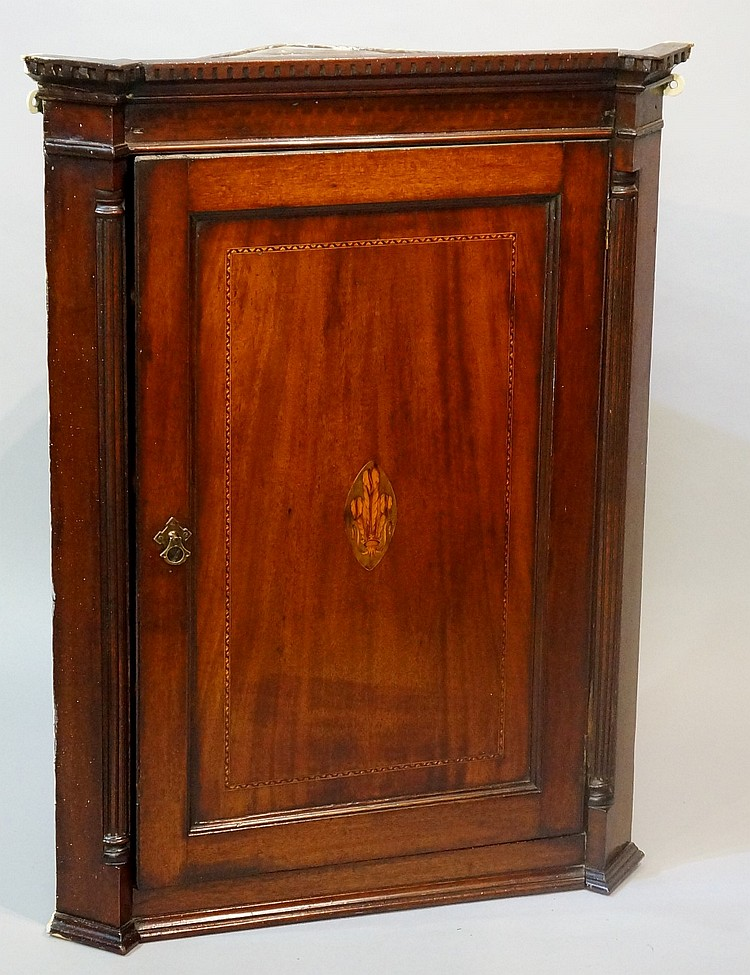 A George III mahogany hanging corner cabinet with dentil carved cornice, en