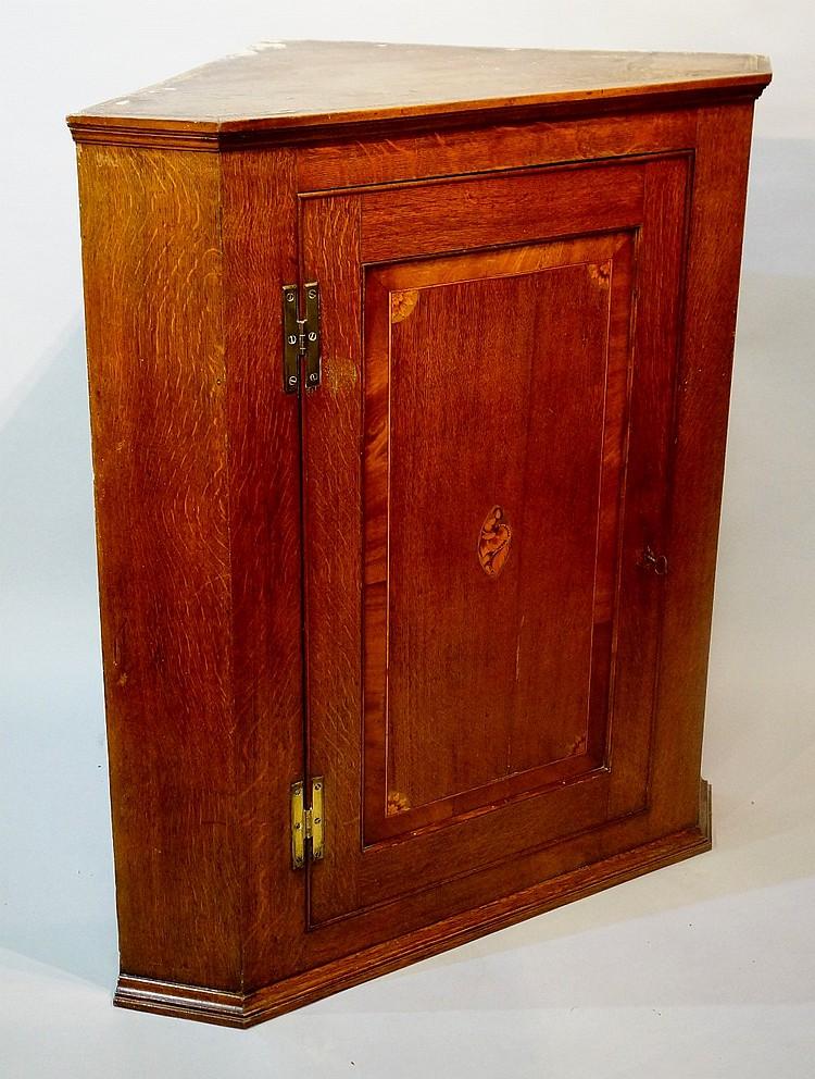 A George III oak hanging corner cupboard, the shallow cornice above plain f